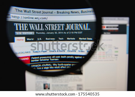 LISBON, PORTUGAL - FEBRUARY 8, 2014: Photo of The Wall Street Journal homepage on a monitor screen through a magnifying glass.