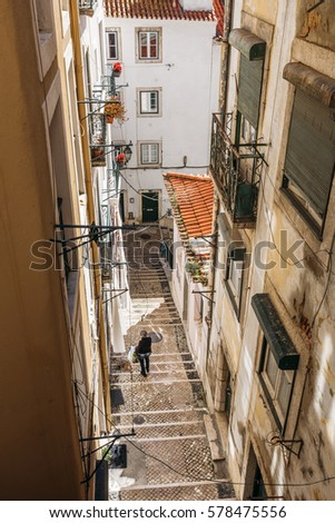 LISBON, PORTUGAL - FEBRUARY 8: woman walking down the narrow street made of stairs in the historical district of Alfama in Lisbon, Portugal on February 8, 2017.