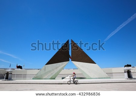 LISBON, PORTUGAL - June 1, 2016: A cyclist going past the ultramar War memorial on a sunny day