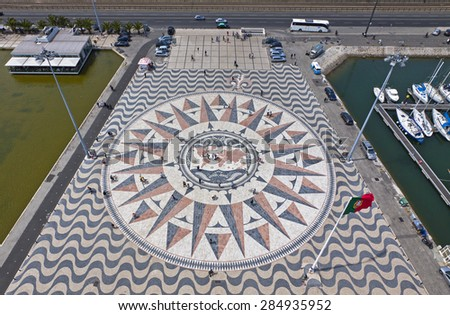 LISBON, PORTUGAL - JUNE 10, 2013: Mosaic map of the Portuguese discoveries and Wind-rose in grey, pink and orange marble bordered by typical Portuguese paving. Belem district of Lisbon city - stock photo