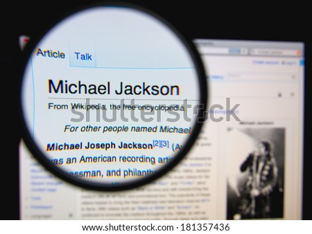 LISBON, PORTUGAL - MARCH 13, 2014: Photo of Wikipedia article page about Michael Jackson on a monitor screen through a magnifying glass. - stock photo