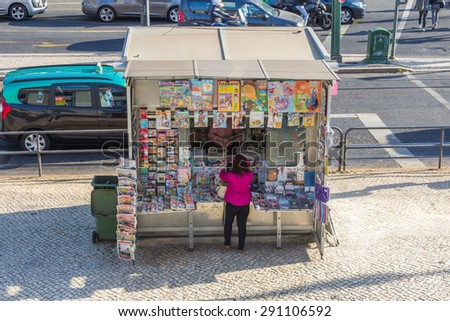 LISBON, PORTUGAL - MAY 24, 2015: An unidentified woman buys newspapers from a small shop next to Cais do Sodre train station in Lisbon, Portugal. - stock photo