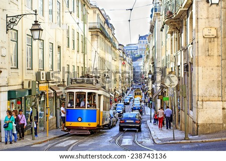 LISBON, PORTUGAL - OCTOBER 27 : Famous tram 28 line in the very center of Lisbon - yellow and blue tramways stop at the tram station, let tourists in and out and take off again on October 27th, 2013 - stock photo