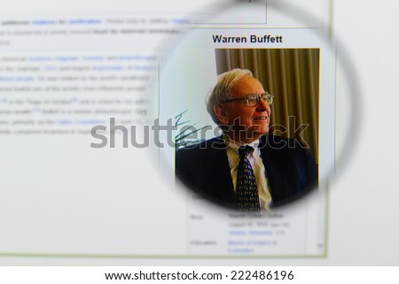 LISBON, PORTUGAL - OCTOBER 8, 2014: Photo of Wikipedia article page about Warren Buffett on a monitor screen through a magnifying glass.   - stock photo
