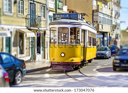 Lisbon yellow tram in the city traffic - stock photo
