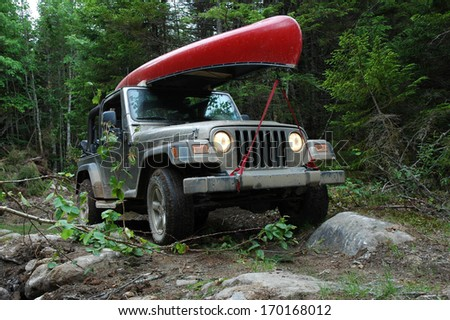 LISCOMB, NOVA SCOTIA - JUNE 15, 2005:  A Jeep Wrangler 4x4 travels through a rough trail in the woods to reach a remote lake for a canoe trip. - stock photo