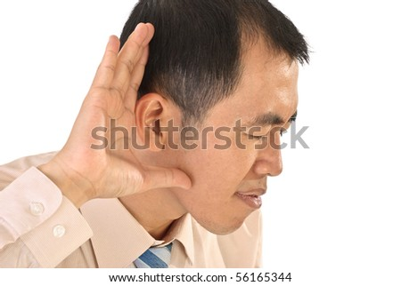 Listen sign with hand on ear, closeup portrait of Asian business man. - stock photo