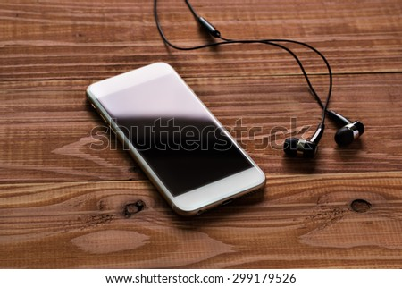 listen the music, smart phone on the table with earphones - stock photo