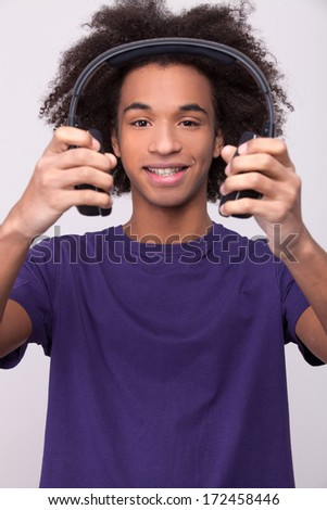 Listen to my favorite song! Cheerful African teenager holding headphones and smiling at camera while standing isolated on grey background - stock photo