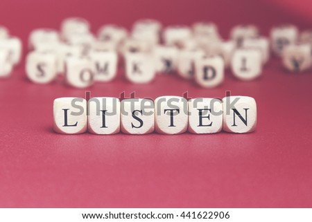 Listen word written on wood cube with red background