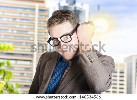 Listening businessman lighting the way of innovation with glowing light bulb attached to ear. Ideas and solutions - stock photo