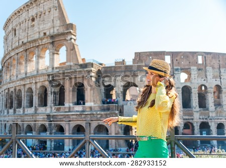 Listening to a bit of opera as she tours Rome... What a magical city Rome is. A happy tourist stands readjusting her earbuds as she smiles into the distance, listening to music near Rome's Colosseum. - stock photo