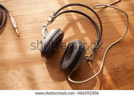 Listening to music. Headphones on a wooden desk.