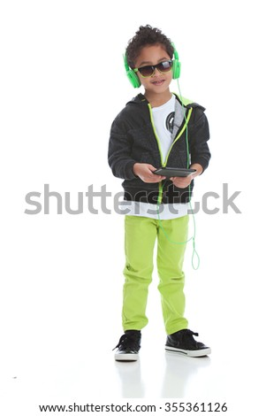 Listening to Music.  Mixed race boy wearing headphones and holding a tablet.  Isolated on white. - stock photo