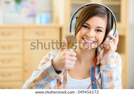 Listening to music. Smiling positive teenage girl listening to music with her headset. - stock photo