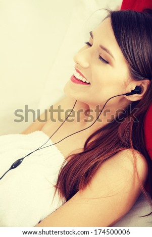 Listening to music. Young woman relaxing at home after bath, listening to music, lying on sofa in towel.  - stock photo
