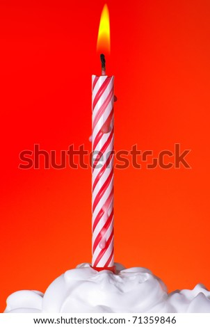 Lit birthday candle on orange background