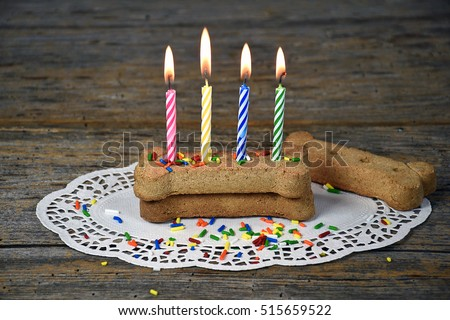 lit birthday candles in dog bone on lacy paper doily
