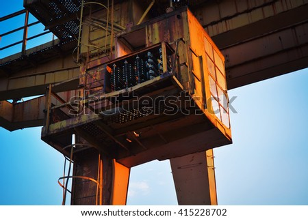 Lit by the sunset rusty cargo bridge crane on rails. An old abandoned decaying portal crane. A plundered gantry crane left to the elements of the nature. - stock photo