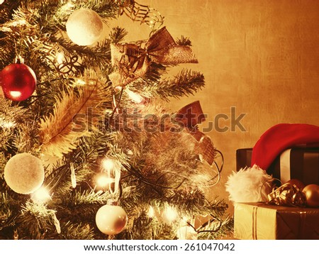 Lit Christmas tree with gifts and santa hat - stock photo