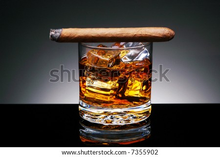 Lit Cigar resting on Glass of Whiskey and Ice cubes on a black reflective surface and light to dark gray background.Horizontal format - stock photo