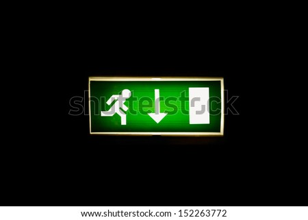 Lit Emergency Exit Sign on a Black Background - stock photo