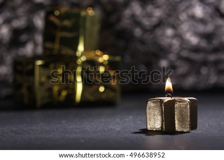 Lit golden advent candle, on a dark black slate underground, low key lighting, shallow depth of field with glitter and gift boxes in background.