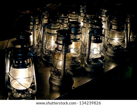 Lit hurricane lamps; background of many lit storm lanterns or hurricane lamps