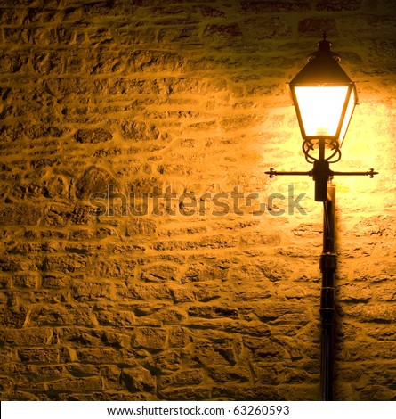 Lit Lamp post against a textured brick wall at night - stock photo