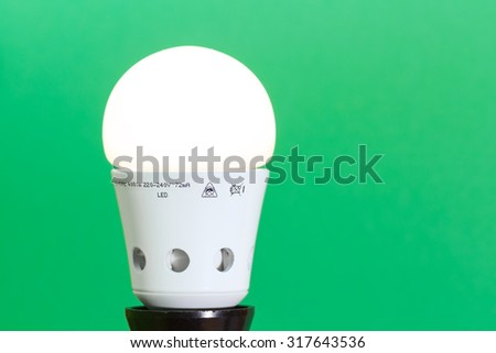 Lit LED light bulb against green background; sustainable use of electrical power concept  - stock photo