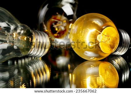 lit light bulb with two unlit ones closeup on black - stock photo