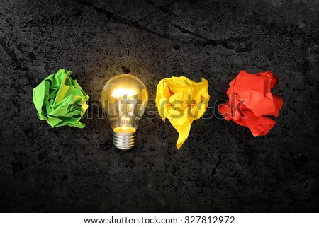 lit lightbulb with crumpled paper balls, idea or inspiration concept - stock photo