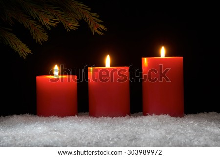 Lit red candles on a dark wooden floor with black background.
