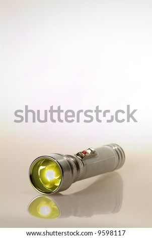 Lit retro flashlight on translucent white background