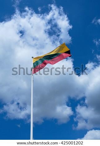Lithuania's flag over cloudy sky - stock photo