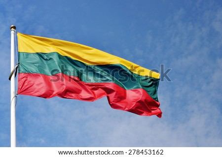 Lithuanian national flag waving on wind against blue cloudy sky - stock photo