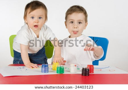 litlle boy and girl enjoy painting with assorted colours