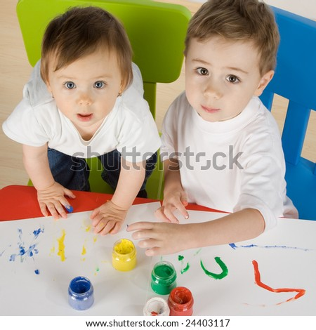 litlle boy and girl enjoy painting with colours and use own hands