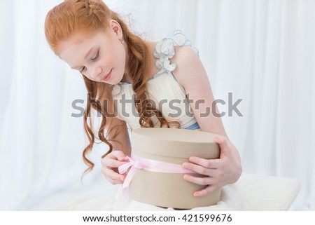 litlle girl sitting on the floor and playing with gift box - stock photo