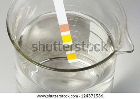 Litmus strips for measurement of acidity.Beaker with water - stock photo