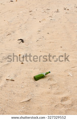 Litter on the beach - Broken bottles and other garbage lying scattered on a beach. - stock photo