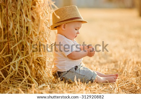 Little adorable baby boy with big brown eyes in a hat sits in a field near haystacks at sunset summer portrait in profile - stock photo
