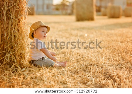 Little adorable baby boy with big brown eyes in a hat sits in a field near haystacks at sunset in summer - stock photo