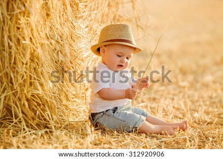 Little adorable baby boy with big brown eyes in a hat sits in a field near haystacks at sunset in summer, and looks at a blade of grass - stock photo