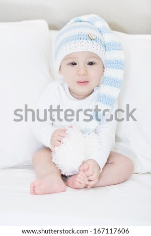 Little, adorable baby in a large white-blue hut, portrait on white sofa