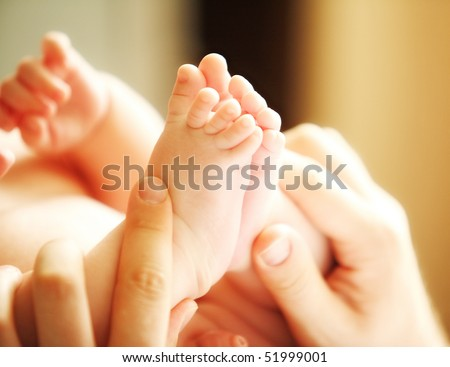 little adorable baby touching his tiny feet - stock photo