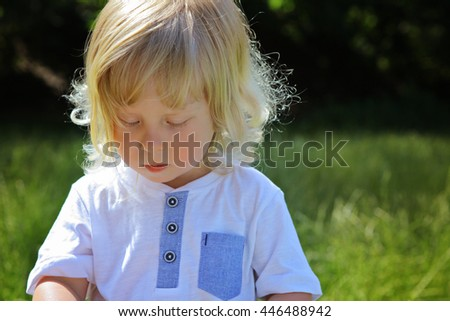little adorable blonde boy wearing casual white and blue t-shirt in park during walk on sunny summer spring day. Young beautiful shy kid looking downwards