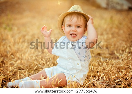 Little adorable  chubby baby boy in a straw hat and a white suit sitting in a field with ears of wheat at sunset in summer - stock photo