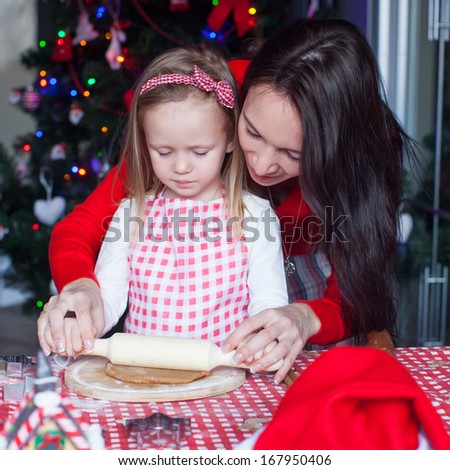 Little adorable girl and young mother baking Christmas gingerbread cookies - stock photo