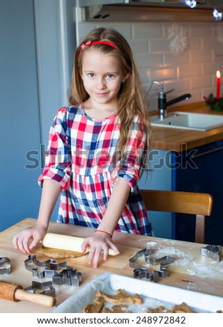 Little adorable girl baking Christmas cookies at home - stock photo